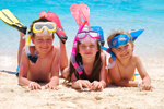 3 kids on a beach with goggles and fins
